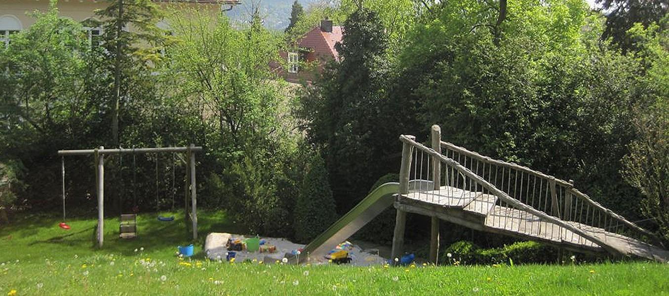 Hausgarten der Familie N mit einer Rutsche, Sandkasten und einer Schaukel