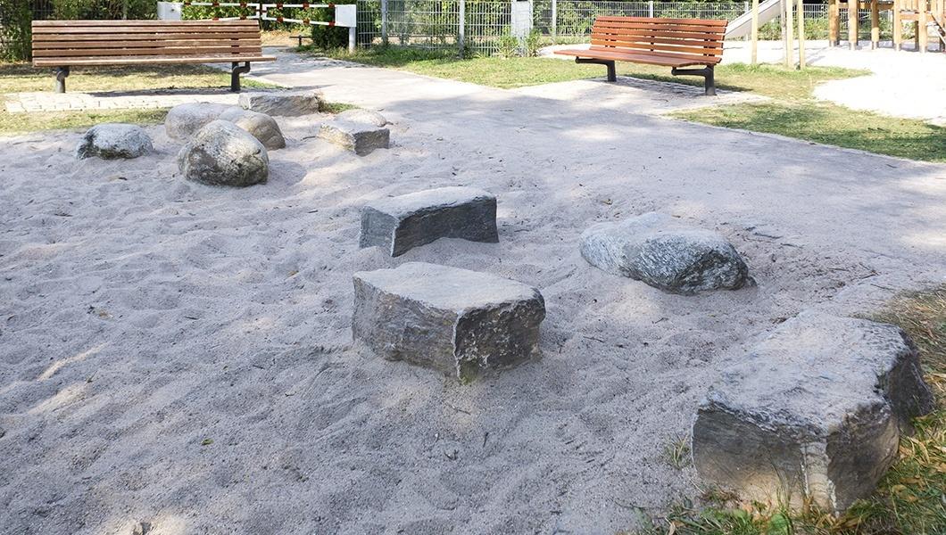 Foto vom Sandkasten mit Sand und großen Steinen auf dem Spielplatz im Lauter Park